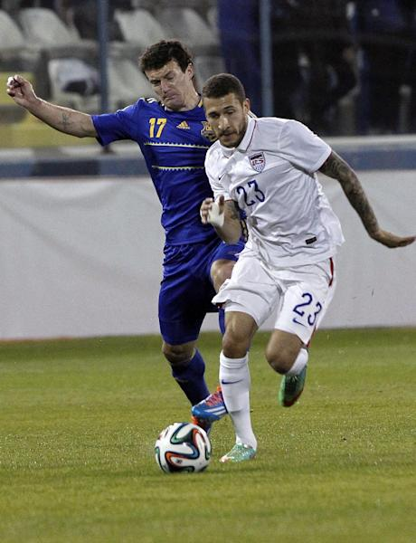 Ukraine's Artem Fedets'kyy, left, fights for the ball with Fabian Johnson of the U.S. during an international friendly soccer match at Antonis Papadopoulos stadium in southern city of Larnaca, Cyprus, Wednesday, March 5, 2014. The Ukrainians are to face the United States in a friendly on Wednesday in Cyprus, a match moved from Kharkiv to Larnaca for security reasons. (AP Photo/Petros Karadjias)