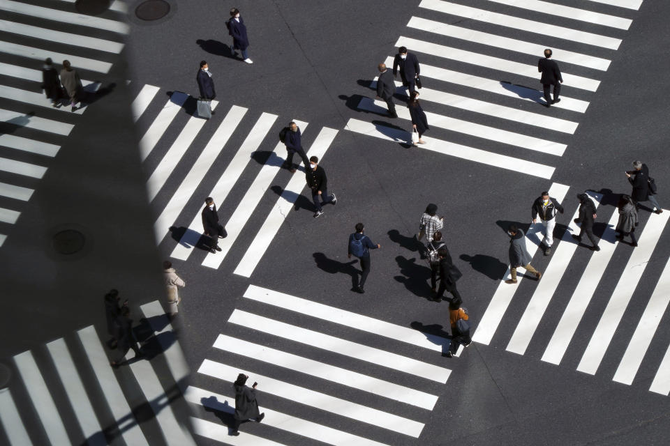 People wearing protective masks to help curb the spread of the coronavirus walk along a pedestrian crossing Wednesday, March 3, 2021, in Tokyo. The Japanese capital confirmed more than 310 new coronavirus cases on Wednesday. (AP Photo/Eugene Hoshiko)