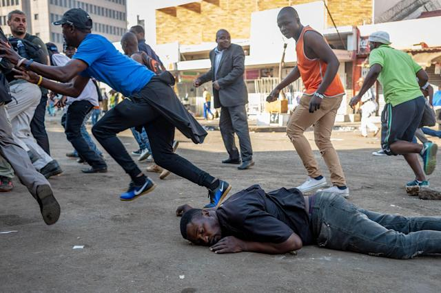 <p>A man who was shot in the back by a live round fired by the Zimbabwean Army lies on the ground bleeding during a protest against the vote count in Harare, Zimbabwe, 01 August 2018. The Zimbabwean army refused to allow journalists to treat the man and attempted to arrest them. (Photo: Yeshiel Panchia/EPA-EFE/REX/Shutterstock) </p>