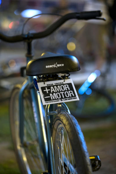 """In this Nov. 28, 2012 photo, a sign decorates a bicycle that reads in Spanish """"More love, less motor"""" in Buenos Aires, Argentina. Civic leaders have tried to make Buenos Aires a bicycle-friendly city, but that's been stymied by another government initiative, protectionist import bans designed to spur domestic production that have instead strangled supplies of everything from bananas to prescription drugs. For cyclists, fewer bikes are available because the business has mostly relied on foreign-made parts. (AP Photo/Natacha Pisarenko)"""