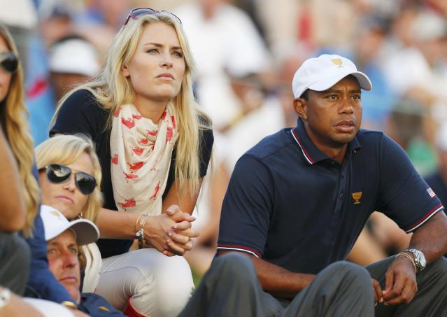 U.S. golfer Tiger Woods and girlfriend Lindsey Vonn sit with teammate Phil Mickelson and Phil's wife Amy (L) as they watch play during the opening Four-ball matches for the 2013 Presidents Cup golf tournament at Muirfield Village Golf Club in Dublin, Ohio October 3, 2013. REUTERS/Chris Keane (UNITED STATES - Tags: SPORT GOLF)