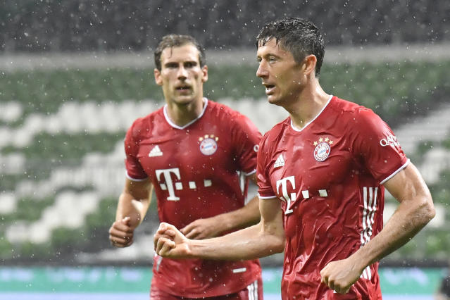 Bayern's Robert Lewandowski, right, celebrates after scoring his side's opening goal during the German Bundesliga soccer match between Werder Bremen and Bayern Munich in Bremen, Germany, Tuesday, June 16, 2020. Because of the coronavirus outbreak all soccer matches of the German Bundesliga take place without spectators. (AP Photo/Martin Meissner, Pool)