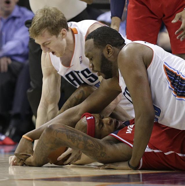 Washington Wizards' Al Harrington, bottom, tries to keep a loose ball as Charlotte Bobcats' Cody Zeller, top left, and Al Jefferson, top right, try to take it away during the second half of an NBA basketball game in Charlotte, N.C., Monday, March 31, 2014. The Bobcats won 100-94. (AP Photo/Chuck Burton)