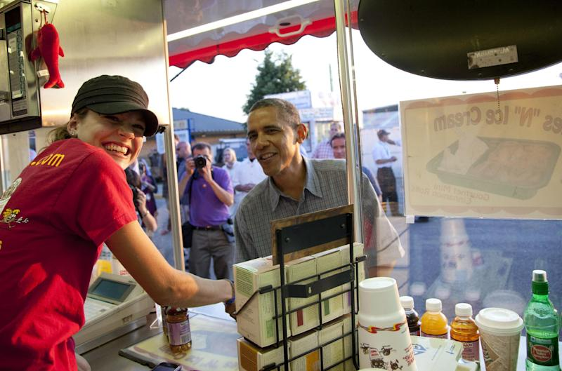 """President Barack Obama visits Cookie Smith at the """"CinnieSmiths"""" mini cinnamon roll stand at the Iowa State Fair, Monday, Aug. 13, 2012, in Des Moines, Iowa. The president is on a three-day campaign bus tour through Iowa. (AP Photo/Carolyn Kaster)"""