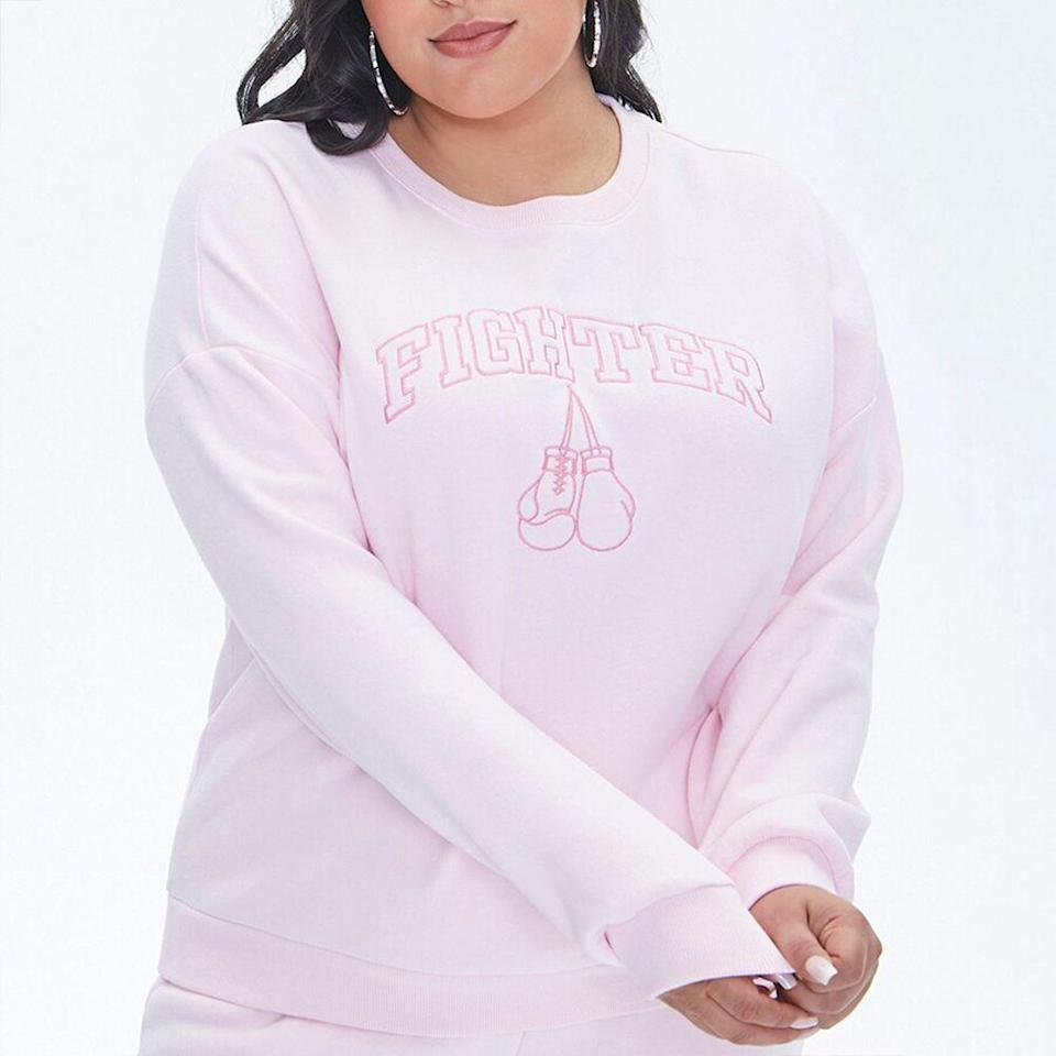 """<p><strong>Forever 21</strong></p><p>forever21.com</p><p><strong>$19.99</strong></p><p><a href=""""https://go.redirectingat.com?id=74968X1596630&url=https%3A%2F%2Fwww.forever21.com%2Fus%2Fshop%2Fcatalog%2Fproduct%2Fplus%2Fwomen-new-arrivals%2F2000413630&sref=https%3A%2F%2Fwww.prevention.com%2Flife%2Fg34387434%2Fbreast-cancer-shirts-clothing%2F"""" rel=""""nofollow noopener"""" target=""""_blank"""" data-ylk=""""slk:Shop Now"""" class=""""link rapid-noclick-resp"""">Shop Now</a></p><p>Whether you're battling breast cancer or know someone who is, this long-sleeve pullover calls it like it is. This has """"Fighter"""" embroidered on the front above two boxing mitts. The sweater is super encouraging and is just plain ol' cute. In collaboration with <a href=""""https://standuptocancer.org/"""" rel=""""nofollow noopener"""" target=""""_blank"""" data-ylk=""""slk:Stand Up to Cancer,"""" class=""""link rapid-noclick-resp"""">Stand Up to Cancer,</a> for each item sold, the retailer will donate 20% of the sweater's proceeds to the organization, as well as flat $5,000 contribution. </p>"""