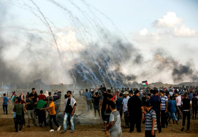 Palestinian protesters watch as tear gas grenades fired by Israeli forces fall during clashes following a demonstration along the Israel-Gaza border