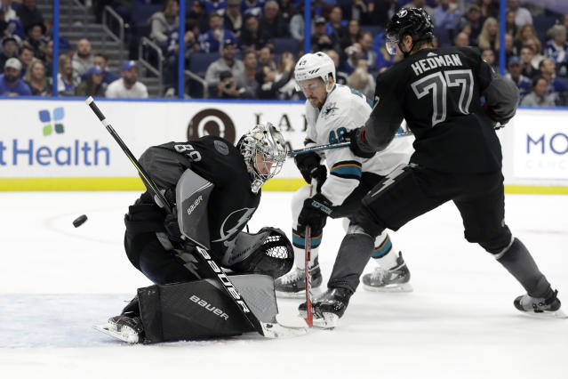 Tampa Bay Lightning goaltender Andrei Vasilevskiy (88) makes a save on a shot as defenseman Victor Hedman (77) keeps San Jose Sharks center Tomas Hertl (48) from a rebound during the third period of an NHL hockey game Saturday, Dec. 7, 2019, in Tampa, Fla. (AP Photo/Chris O'Meara)