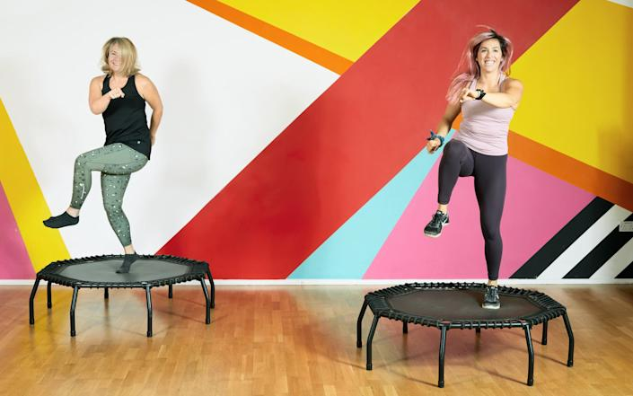 two women bounce on trampolines - Owen Harvey