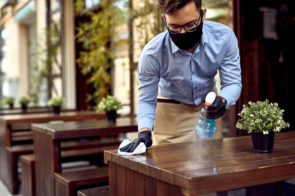 A worker disinfecting tables at a restaurant.