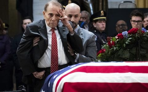 Former Senator Bob Dole stands up and salutes the casket of the late former President George HW Bush - Credit: Getty