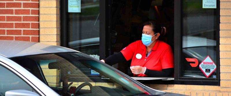 Denver, CO, USA. May 12, 2020. Fast food worker at Chick-Fil-A restaurant in Denver serving food to a drive thru customer while wearing her face mask.