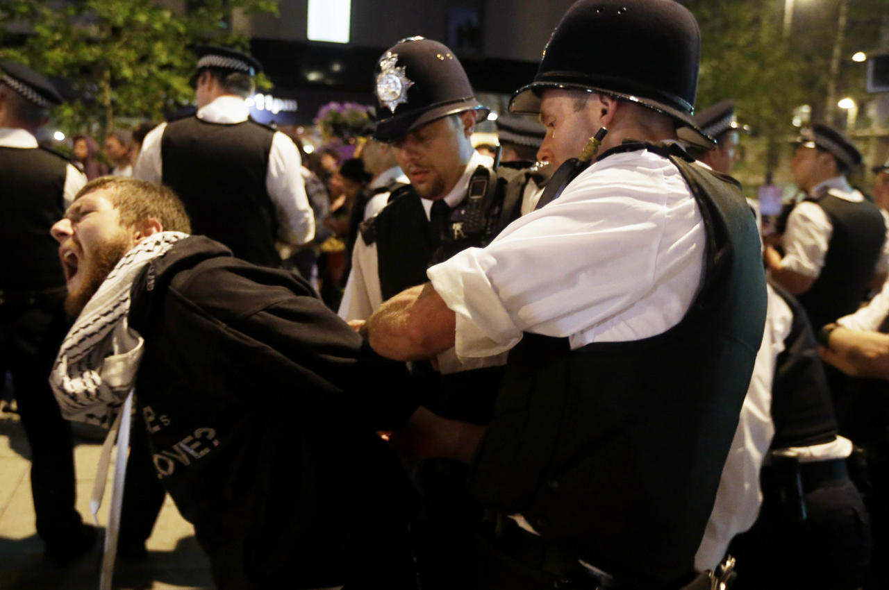 A cyclist is arrested after a protest outside the Olympic Park during the 2012 Summer Olympics Opening Ceremony, Friday, July 27, 2012, in London. (AP Photo/Matt Rourke)
