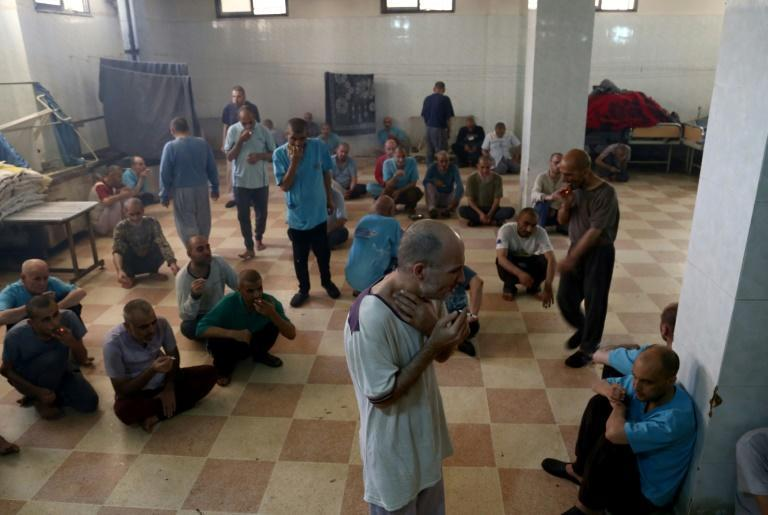 Syrian patients smoke cigarettes in a room at the mental health clinic near the border with Turkey, on July 6, 2017