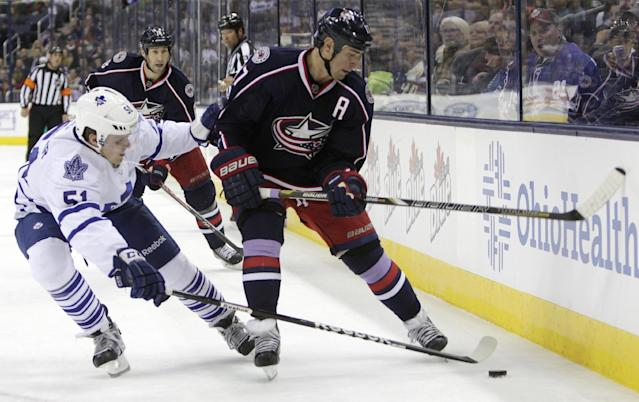 Columbus Blue Jackets' Brandon Dubinsky, right, tries to pass the puck past Toronto Maple Leafs' Jake Gardiner during the second period of an NHL hockey game on Friday, Oct. 25, 2013, in Columbus, Ohio. (AP Photo/Jay LaPrete)