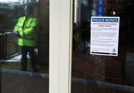 A police officer is reflected in a window next to a notice about former Russian intelligence officer Sergei Skripal and his daughter Yulia who were found on a park bench after being poisoned in Salisbury