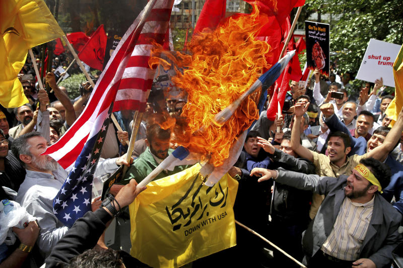"Demonstrators burn Israeli and U.S. flags to show their anger over the deaths of nearly 60 Palestinians along the Gaza border on Monday, during a protest inside the former U.S. embassy in Tehran, Iran, Wednesday, May 16, 2018. State media reported that Iran's President Hassan Rouhani has condemned the killing of Palestinians by Israel, saying ""Palestinians are fighting for their homeland."" (AP Photo/Ebrahim Noroozi)"