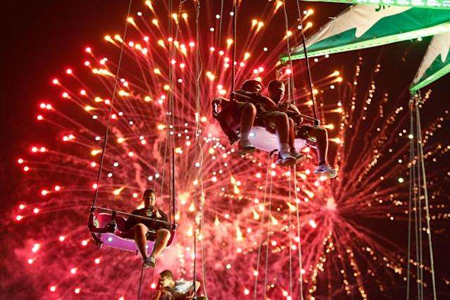<p>People hang from the Sky Flyer ride at the State Fair Meadowlands during a Fourth of July fireworks display, Friday, July 3, 2015, in East Rutherford, N.J. (Photo: Julio Cortez/AP) </p>