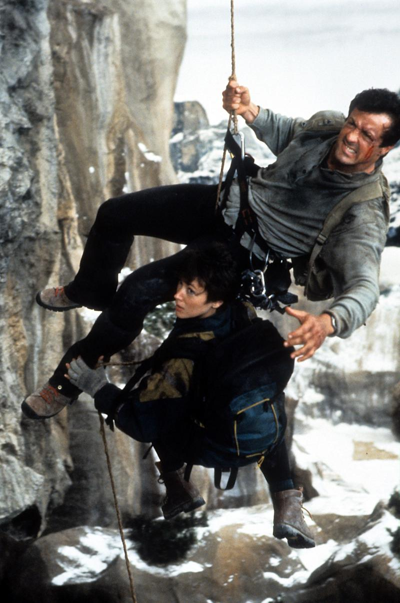 Sylvester Stallone and Janine Turner hanging by ropes off the side of a cliff in a scene from the film 'Cliffhanger', 1993. (Photo by Carolco Pictures/Getty Images)