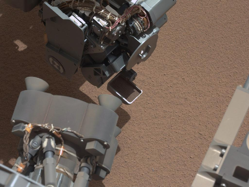 This image from the right Mast Camera (Mastcam) of NASA's Mars rover Curiosity shows a scoop full of sand and dust lifted by the rover's first use of the scoop on its robotic arm. In the foreground, near the bottom of the image, a bright object is visible on the ground. The object might be a piece of rover hardware. (NASA)