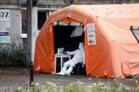 A health worker in protective suit waits for people at a test center in Warsaw