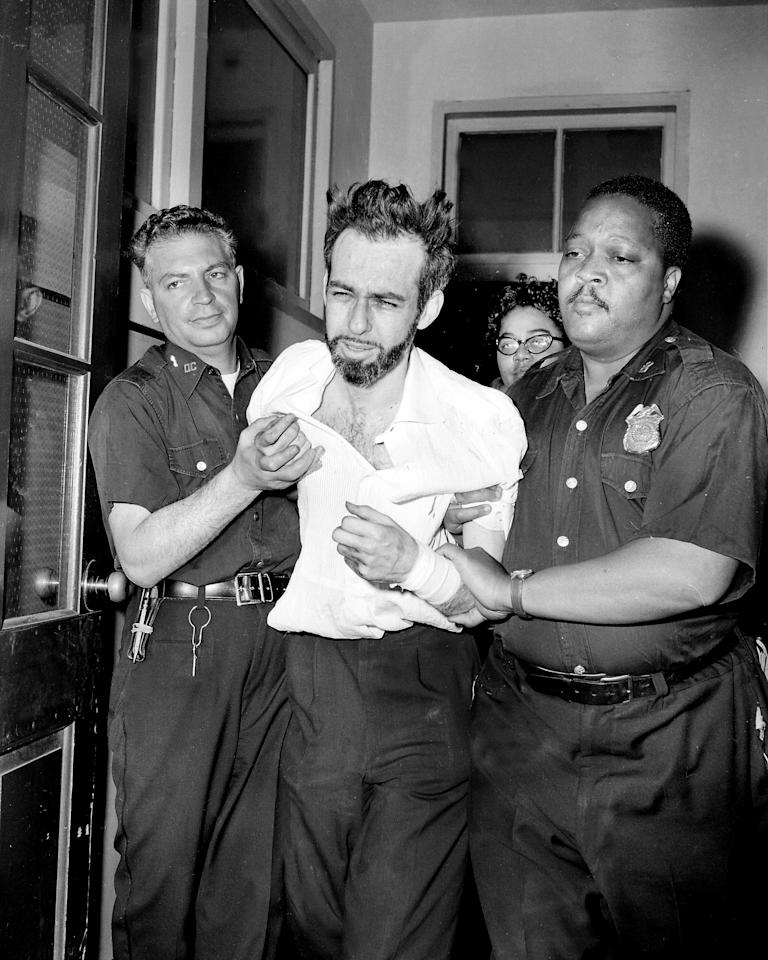 Trying to fight free of police guard. Burton Pugach is taken from Morrisania Hospital, where he was treated for self-inflicted slashes on both wrists. The disbarred lawyer, on trial for lye attck on his former girl friend, Linda Riss, cut wrists with his broken eyeglass lens minuted before his trial was to proceed in Bronx County Court, June 15, 1961. Total of 21 stitches were taken.  (Photo by Ossie LeViness/NY Daily News Archive via Getty Images)
