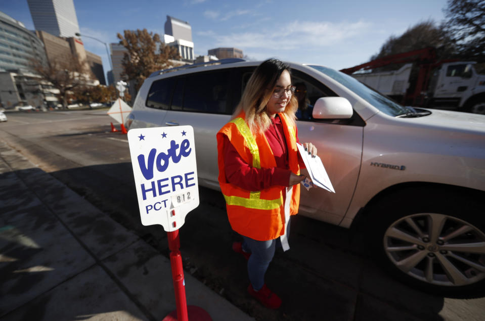 Election judge Amanda Vigil collects a ballot from a motorist at the drive-through site of the Denver Elections Division outside the City/County Building early Tuesday, Nov. 5, 2019, in Denver. (AP Photo/David Zalubowski)
