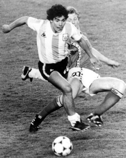 FILE - In this June 13, 1982 file photo, Argentina's Diego Maradona, front, is attacked by Belgium's Guy Vandermissen during the opening game of the Soccer World Cup in Barcelona, Spain. The Argentine soccer great who was among the best players ever and who led his country to the 1986 World Cup title before later struggling with cocaine use and obesity, died from a heart attack on Wednesday, Nov. 25, 2020, at home in Buenos Aires. He was 60. (AP Photo, File)