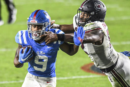 Mississippi running back Jerrion Ealy (9) is tackled by South Carolina defensive lineman Kingsley Enagbare (52) during the second half of an NCAA college football game in Oxford, Miss., Saturday, Nov. 14, 2020. (AP Photo/Bruce Newman)