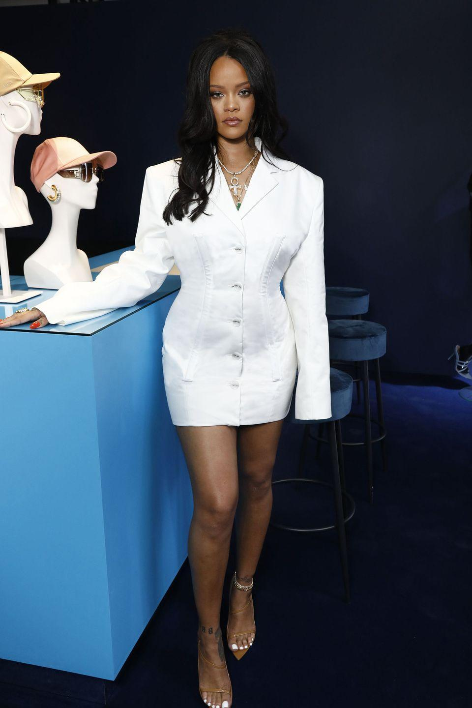 <p>In a white Fenty blazer dress, layered jewelry, ankle bracelets, and nude sandals for the launch of her Fenty fashion line in Paris, France. </p>