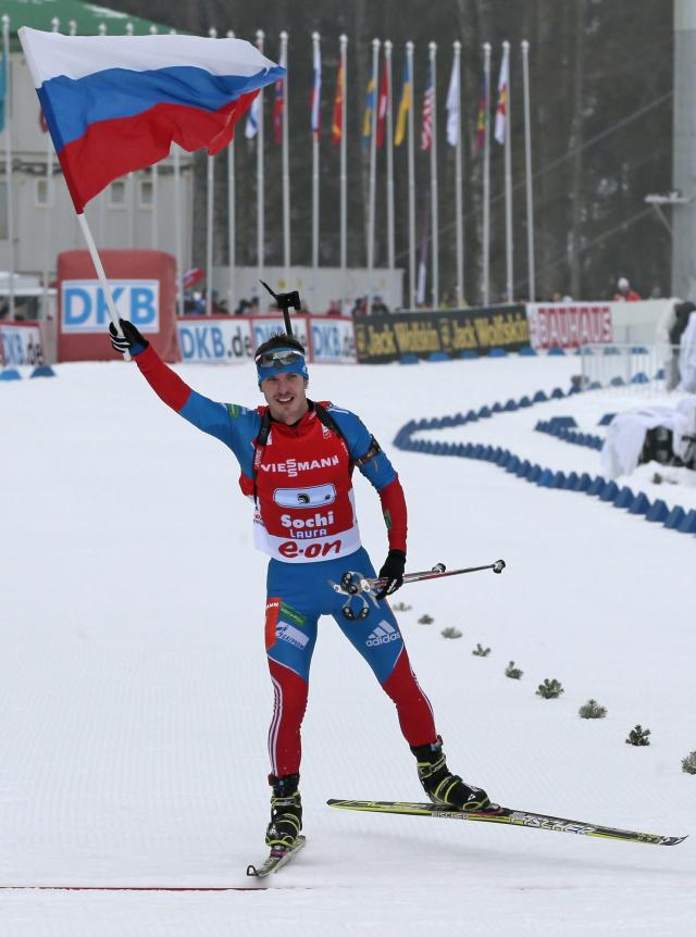 FILE - In this file photo dated Sunday, March 10, 2013, member of the winning Russian relay team Evgeny Ustyugov holds the Russian national flag aloft as he finishes in the men's 4X7.5 km Relay during the IBU World Cup Biathlon in Sochi, Russia. The International Biathlon Union on Saturday Feb. 15, 2020, issued a two-year ban for Russia's Evgeny Ustyugov, who was part of the gold medal-winning mens relay team at the 2014 Sochi Winter Olympics. (AP Photo/Mikhail Metzel, FILE)