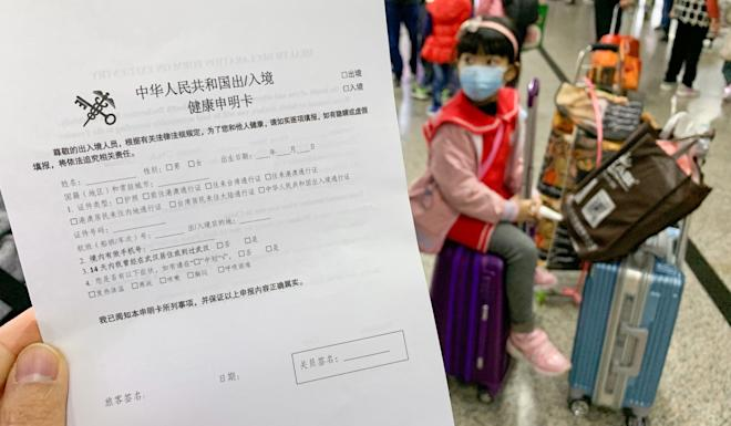 Travellers on the mainland side of the Shenzhen-Hong Kong border fill in health declaration forms from the central government. Photo: Nora Tam