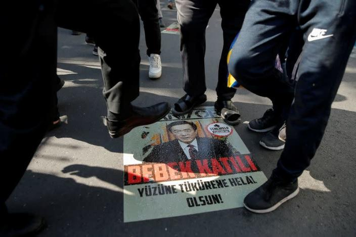 FILE PHOTO: Ethnic Uighur demonstrators step on a poster with an image of Communist Party Secretary of Xinjiang Uighur Autonomous Region Chen Quanguo during a protest against China in front of the Chinese Consulate in Istanbul