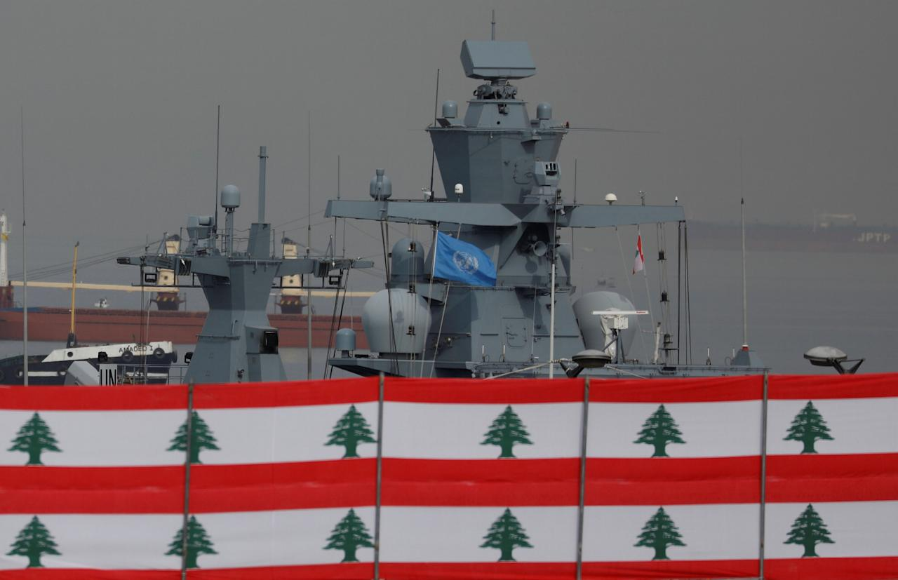 An U.N. vessel is seen over Lebanese flags during the rehearsal military parade for the Independence Day which will be held next Wednesday on November 22 in Beirut, Lebanon, November 18, 2017. REUTERS/Jamal Saidi