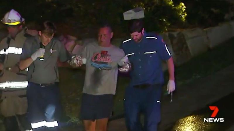 The father leaves the home with his hands covered in bandages. Source: 7 News