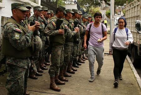 Residents walk as soldiers stand near the Electoral National Council  (CNE) headquarters prior to Sunday presidential election in Quito