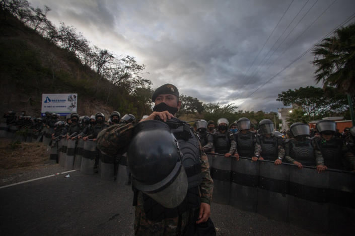 Guatemalan soldiers block the road where Honduran migrants, hoping to reach the U.S. border, rest on the side of a highway in Vado Hondo, Guatemala, Saturday, Jan. 16, 2021. Guatemalan authorities estimated that as many as 9,000 Honduran migrants crossed into Guatemala as part of an effort to form a new caravan to reach the U.S. border. (AP Photo/Sandra Sebastian)