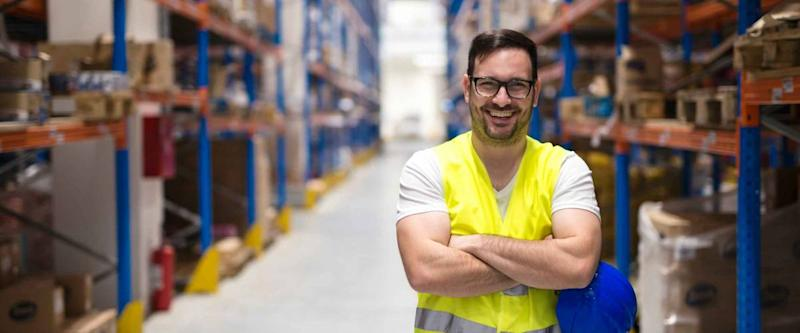Portrait of middle aged caucasian warehouse worker standing in large warehouse distribution center