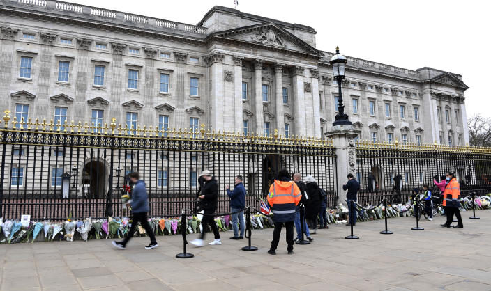 People leave flowers and take photos outside the gates of Buckingham Palace in London, a day after the death of Britain's Prince Philip, Saturday, April 10, 2021. Britain's Prince Philip, the irascible and tough-minded husband of Queen Elizabeth II who spent more than seven decades supporting his wife in a role that mostly defined his life, died on Friday. (AP Photo/Alberto Pezzali)