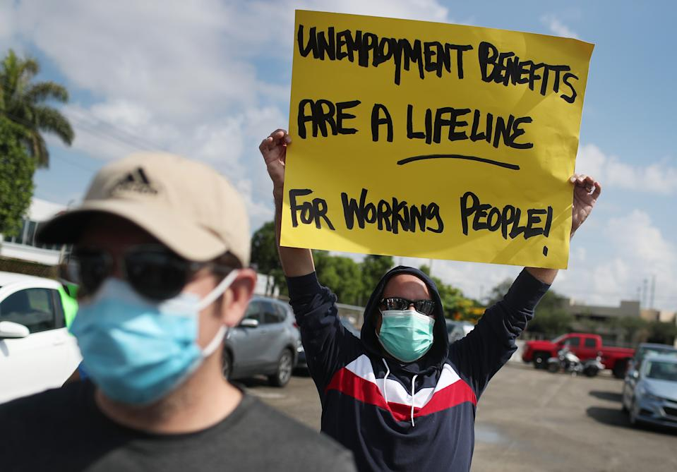MIAMI SPRINGS, FLORIDA - JULY 16: Carlos Ponce joins other demonstrators participating in a protest asking Senators to support the continuation of unemployment benefits on July 16, 2020 in Miami Springs, Florida.  The protesters were asking Senators to support the new Schumer/Wyden legislation that extends unemployment benefits for all laid-off Americans as the coronavirus pandemic continues to disrupt the economy.  (Photo by Joe Raedle/Getty Images)