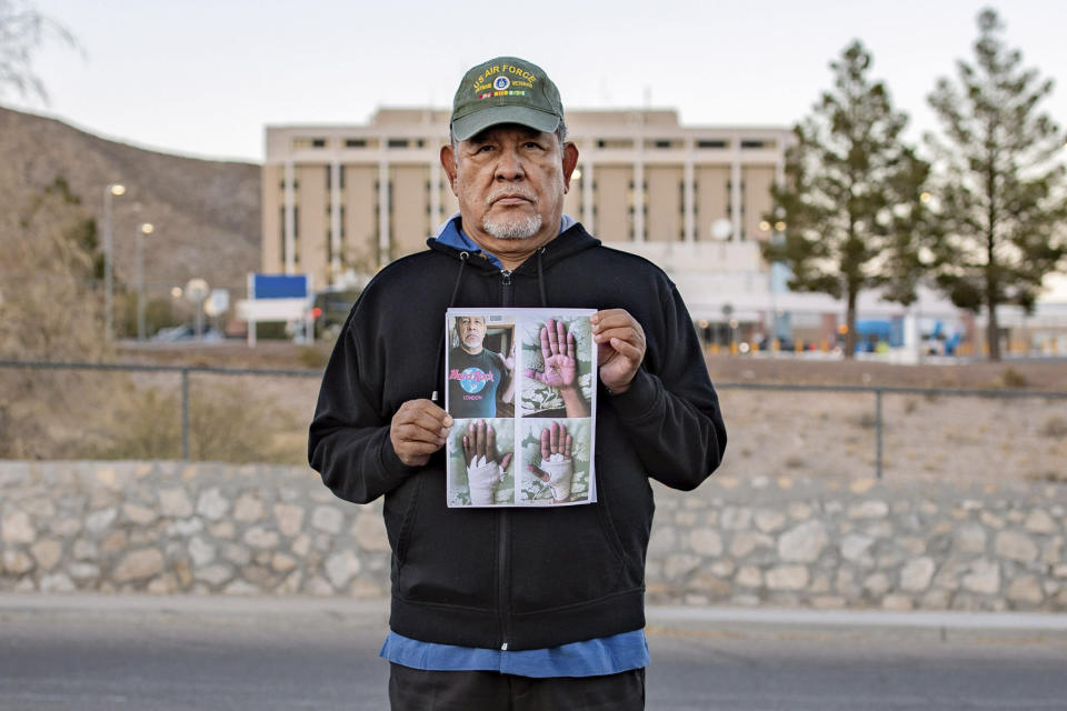 In this undated photo provided by the Institute for Justice, Vietnam veteran José Oliva holds a photo in front of the VA hospital in El Paso, Texas. (Institute for Justice via AP)