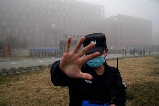 A security person moves journalists away from the Wuhan Institute of Virology after a World Health Organization team arrived for a field visit in Wuhan Feb. 3, 2021.