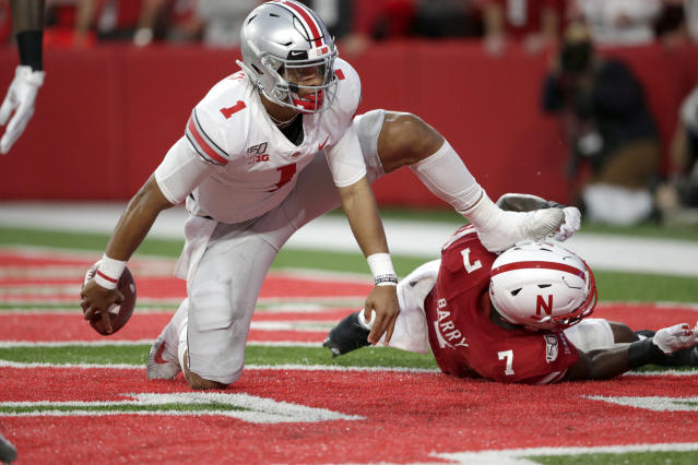 "Ohio State quarterback <a class=""link rapid-noclick-resp"" href=""/ncaaf/players/287612/"" data-ylk=""slk:Justin Fields"">Justin Fields</a> (1) gets up after scoring a touchdown next to Nebraska linebacker Mohamed Barry (7) in Lincoln, Neb., Saturday, Sept. 28, 2019. (AP Photo/Nati Harnik)"