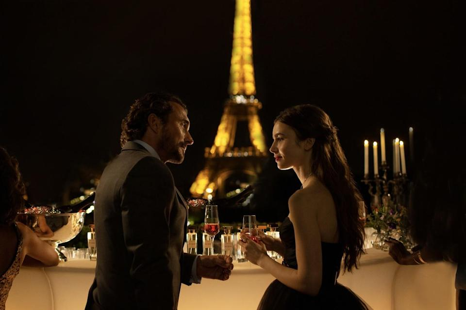 "Two actors talk to each other over drinks in front of the Eiffel Tower in a scene from ""Emily in Paris"""