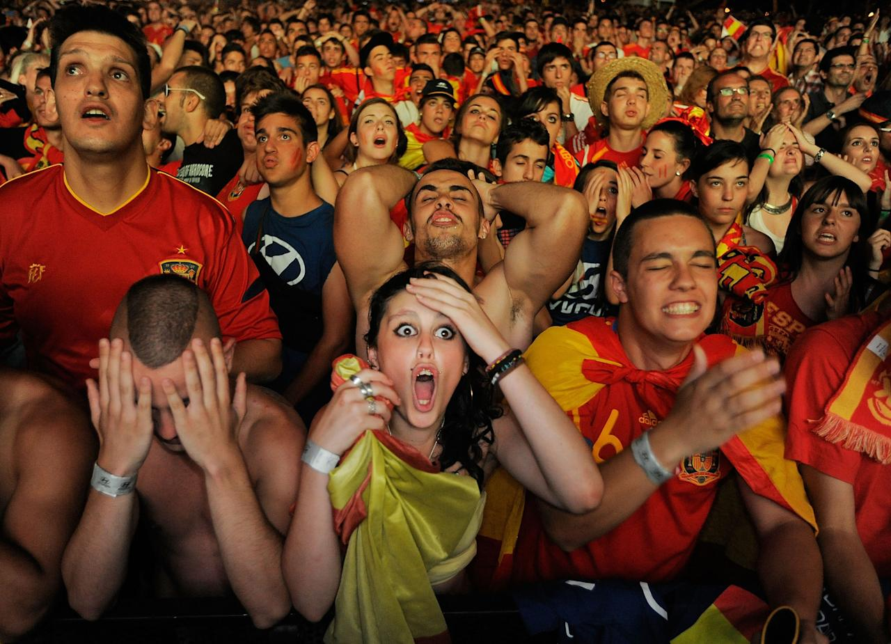 Aficionados españoles siguen el partido de semifinales entre España y Portugal en una calle de Madrid. (Photo by Denis Doyle/Getty Images)