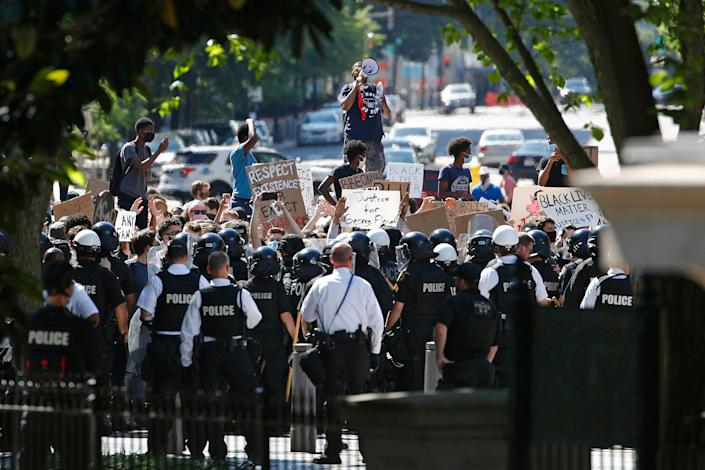 Protesters gather in front of a line of Uniformed U.S. Secret Service officers during a protest about the death of George Floyd, a black man who died in police custody in Minneapolis, near the White House, Saturday, May 30, 2020, in Washington.