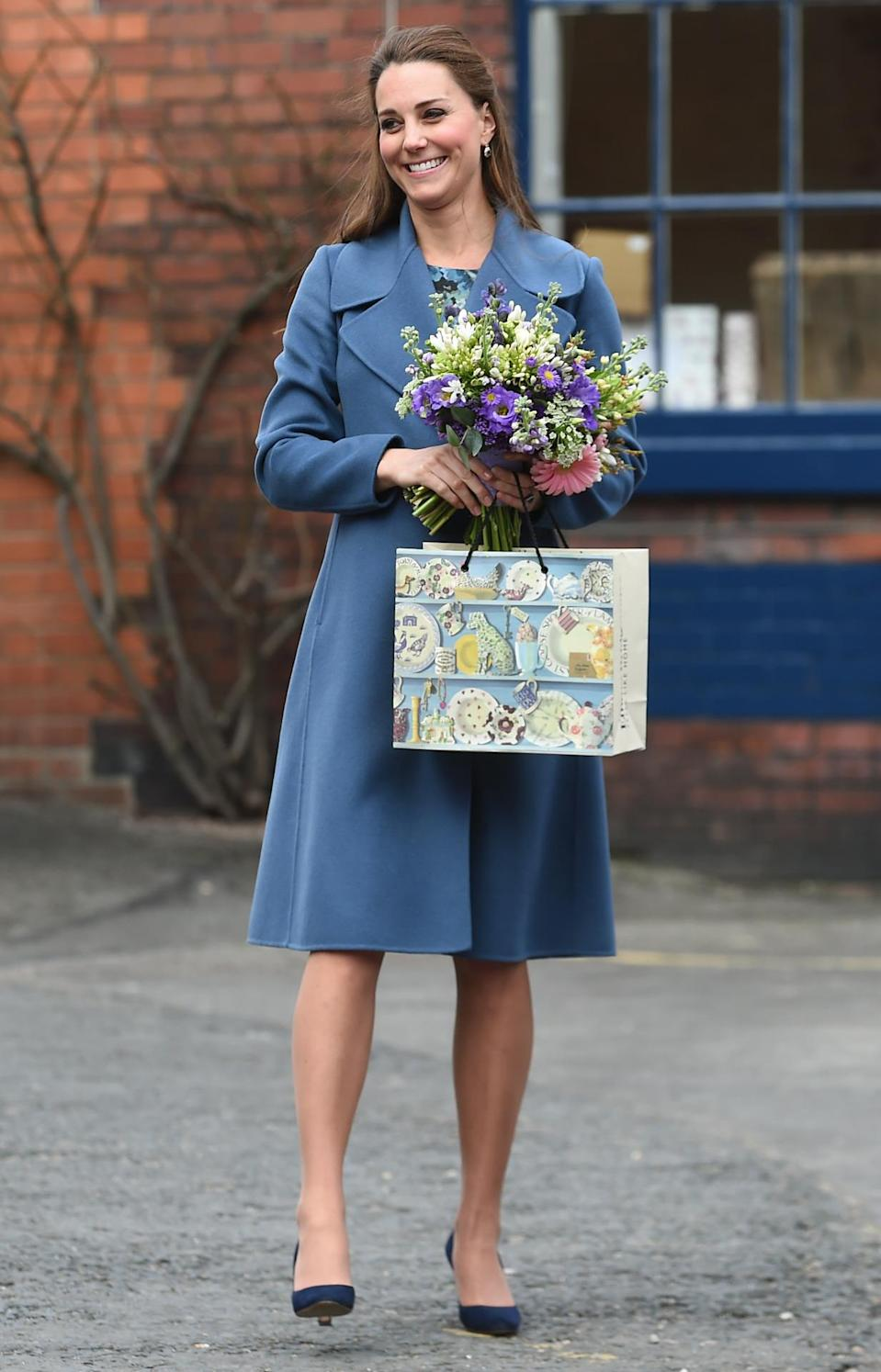 <p>Kate opted for an elegant blue Max Mara coat for a trip to a pottery factory in Staffordshire. The Duchess accessorised with a navy clutch from L.K. Bennett and suede heels by Jimmy Choo. </p><p><i>[Photo: PA]</i></p>