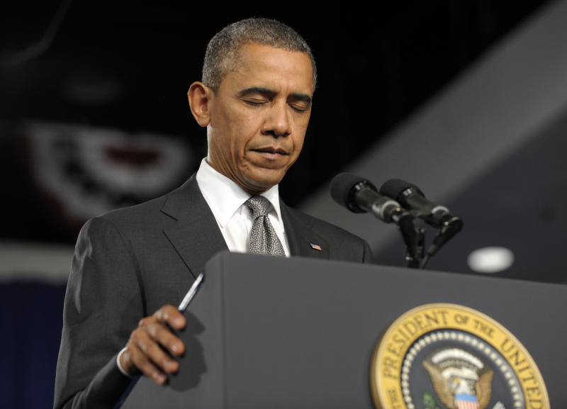 President Barack Obama pauses during a moment of silence for the victims of the Aurora, Colo., shooting during an event at the Harborside Event Center in Ft. Myers, Fla., Friday, July 20, 2012. Obama, who was scheduled to spend the day campaigning in Florida, is canceling his next campaign event to return to Washington to monitor the shooting. (AP Photo/Susan Walsh)