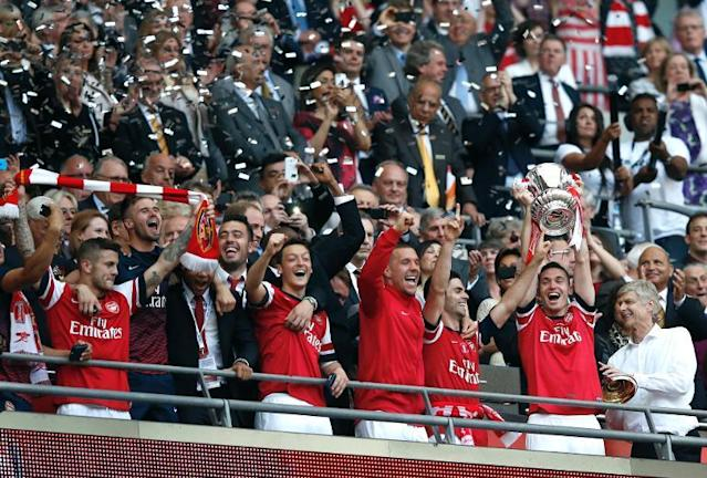 Arsenal's manager Arsene Wenger (R) looks at his players holding the trophy after winning the English FA Cup final match against Hull City at Wembly Stadium in London on May 17, 2014