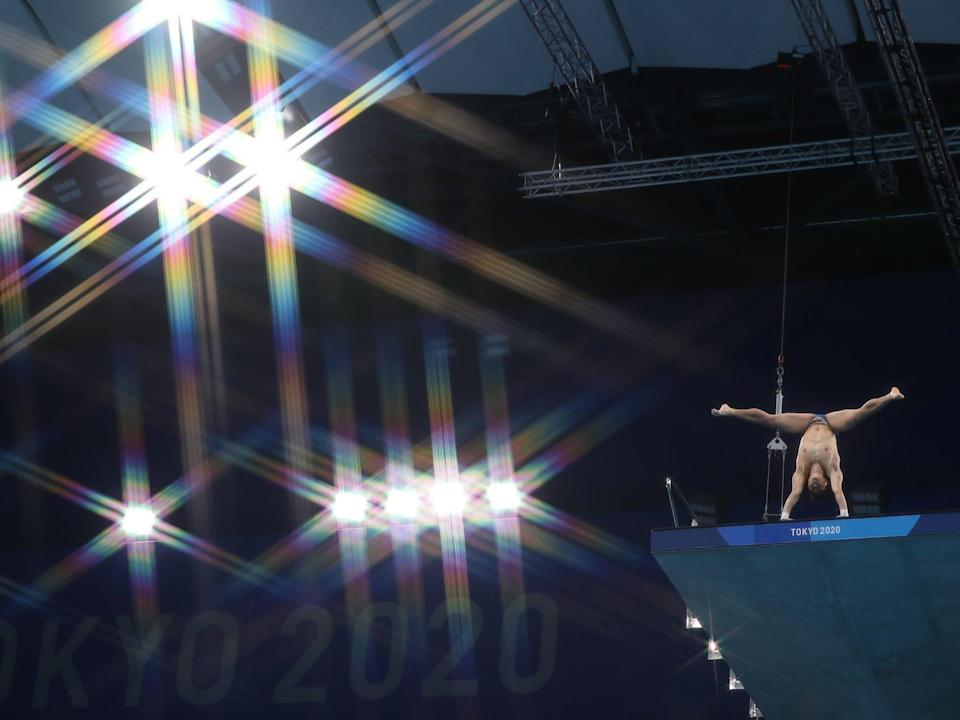 A diver in a handstand on the platform in the 10m diving event at the Tokyo Olympics.