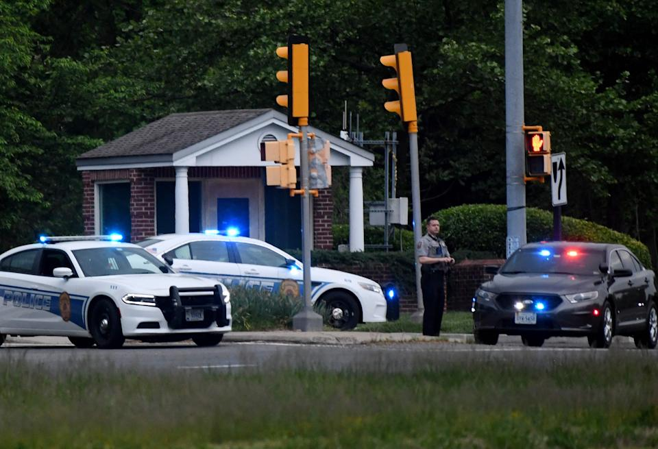 Police cars cluster outside an entrance gate to the CIA's headquarters May 4 in Langley, Va., after an incident involving an armed man.